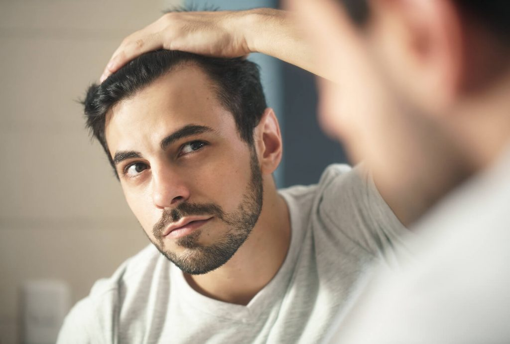 Hair transplant Los Angeles man looking into mirror at hair loss